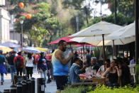 People socialize in the historic center in Mexico City, Saturday, Nov. 14, 2020. Mexico City announced yesterday that restaurants and bars will have to close earlier after the number of people hospitalized for COVID-19 rose to levels not seen since August. (AP Photo/Ginnette Riquelme)