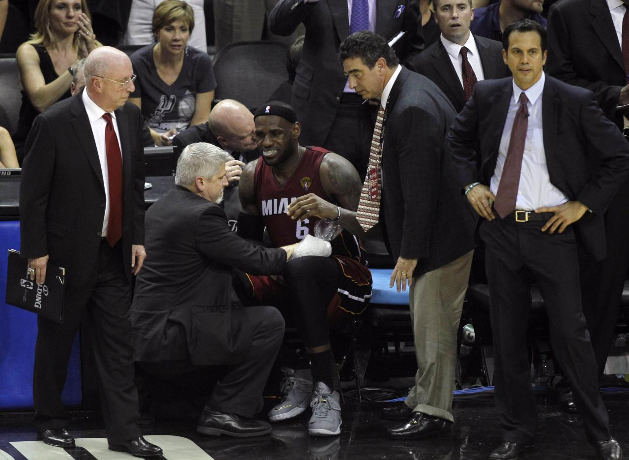 Miami Heat's LeBron James sits on the bench after hurting his leg during the fourth quarter against the San Antonio Spurs in Game 1 of their NBA Finals basketball series in San Antonio, Texas June 5, 2014. REUTERS/Mike Stone (UNITED STATES - Tags: SPORT BASKETBALL)