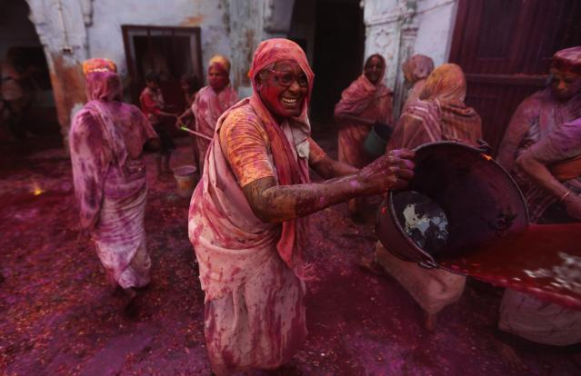 A widow throws coloured water during Holi celebrations organised by non-governmental organisation Sulabh International at a widows' ashram in Vrindavan in the northern Indian state of Uttar Pradesh March 17, 2014. Traditionally in Hindu culture, widows are expected to renounce earthly pleasure so they do not celebrate Holi. But women at the shelter for widows, who have been abandoned by their families, celebrated the festival by throwing flowers and coloured powder. Holi, also known as the Festival of Colours, heralds the beginning of spring and is celebrated all over India. REUTERS/Adnan Abidi (INDIA - Tags: SOCIETY RELIGION)