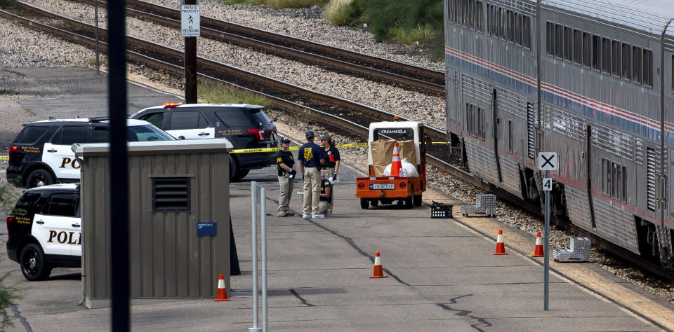 A Federal Bureau of Investigation evidence response team works at the scene of a shooting aboard Amtrak train in downtown Tucson, Ariz., on Monday, Oct. 4, 2021. (Rebecca Sasnett/Arizona Daily Star via AP)