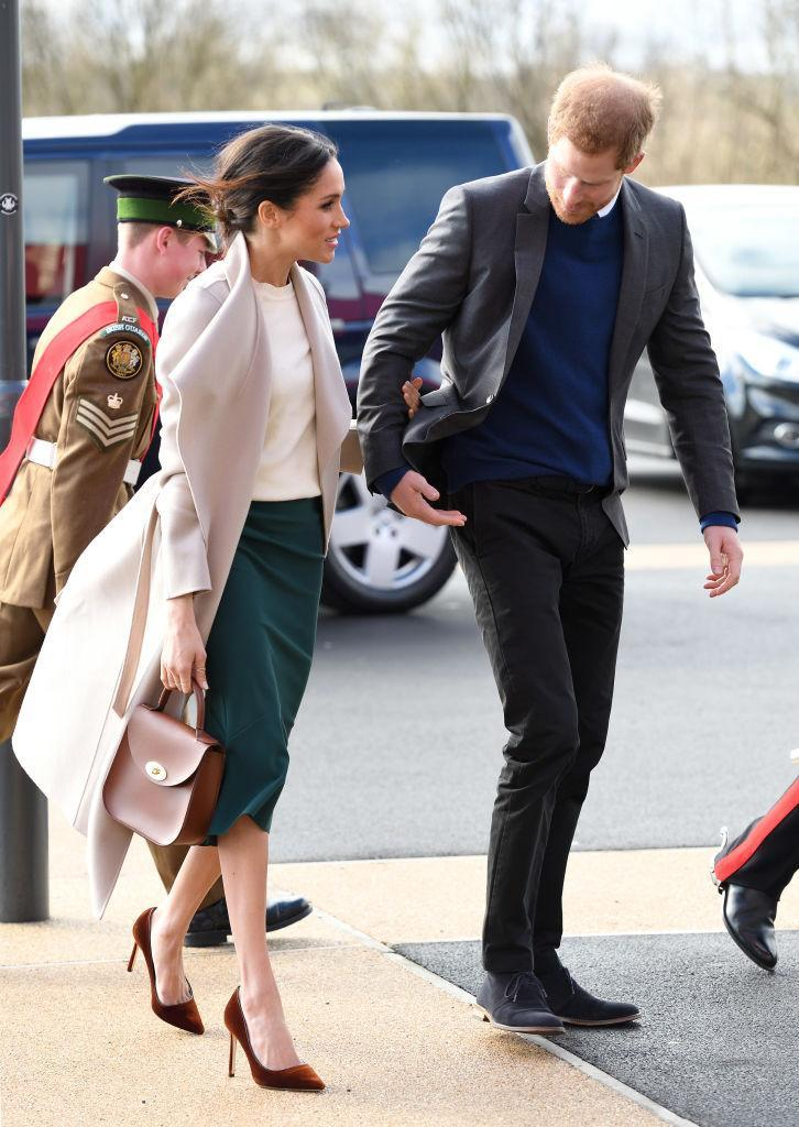 """<p><strong>When: March 23, 2018</strong><br>The 36-year-old paired it with a knee-length hunter green skirt from Greta Constantine underneath a $962 CAD ($475 USD) sand-toned maxi-length coat by one of her favourite <a rel=""""nofollow noopener"""" href=""""https://www.mackage.com/hadia-long-wool-jacket-with-draped-collar-and-sash-tie/HADIA.html?dwvar_HADIA_color=COL640&cgid=women-wools#start=2&cgid=women-wools"""" target=""""_blank"""" data-ylk=""""slk:Canadian labels, Mackage"""" class=""""link rapid-noclick-resp"""">Canadian labels, Mackage</a>. Markle accessorized with a Charlotte Elizabeth cognac bag and velvet Jimmy Choo heels. <em>(Photo: Getty)</em> </p>"""