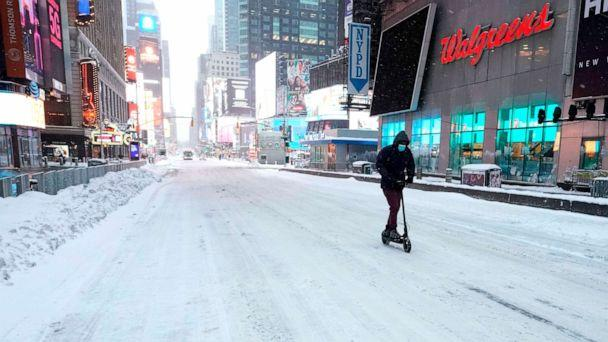 PHOTO: TOPSHOT - A man travels on a scooter in Times Square on Dec. 17, 2020 in New York, the morning after a powerful winter storm hit the U.S. (Timothy A. Clary/AFP via Getty Images)