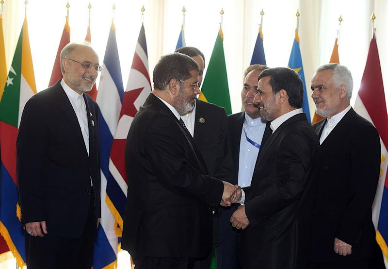 "In this photo released by the official website of the Iranian presidency office, Iranian President Mahmoud Ahmadinejad, second right, welcomes Egyptian President Mohammed Morsi for the opening session of the Nonaligned Movement, NAM, summit, in Tehran, Iran, Thursday, Aug. 30, 2012. Morsi described the Syrian regime as ""oppressive"" and called for it to transfer power to a democratic system during a visit to Syria's key regional ally Iran on Thursday. Iranian Vice-President Mohammad Reza Rahimi stands at right, and Foreign Minister Ali Akbar Salehi, left. (AP Photo/Presidency Office)"