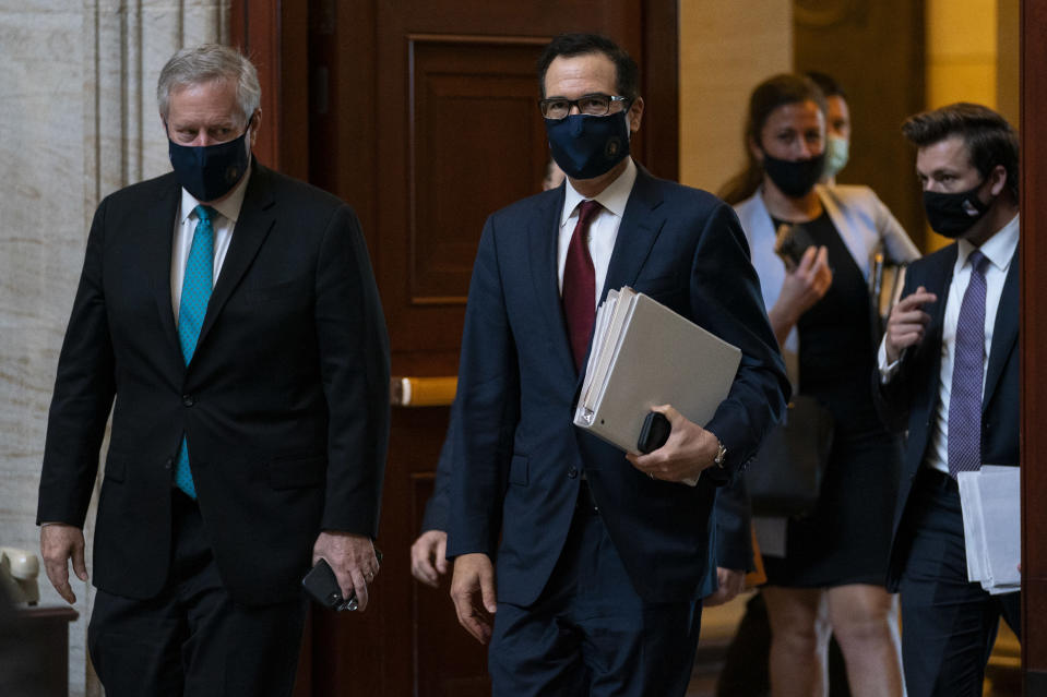 Treasury Secretary Steven Mnuchin, center, and White House chief of staff Mark Meadows, left, walk to House Speaker Nancy Pelosi's office on Capitol Hill in Washington, Wednesday, Aug. 5, 2020. Some clarity is beginning to emerge from the bipartisan Washington talks on a huge COVID-19 response bill. An exchange of offers and meeting devoted to the Postal Service on Wednesday indicates the White House is moving slightly in House Speaker Nancy Pelosi's direction on issues like aid to states and local governments and unemployment insurance benefits. But the negotiations have a long ways to go. (AP Photo/Carolyn Kaster)