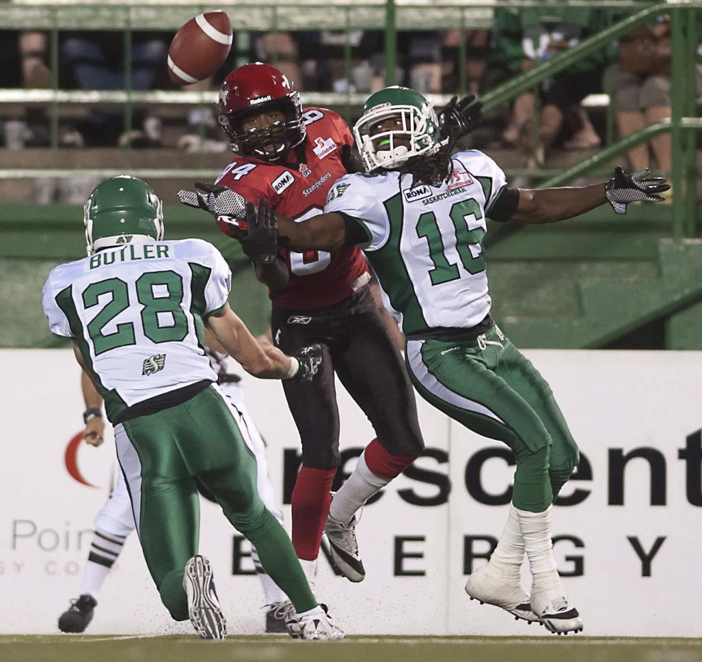 Saskatchewan Roughriders defensive back Eddie Russ (right) intercepts a pass intended for Calgary Stampeders receiver Landan Talley while Craig Butler looks on during the second half of CFL pre-season football action in Regina, Sask., Friday, June 22, 2012. The Stamps defeated the Riders 33-31. THE CANADIAN PRESS/Liam Richards