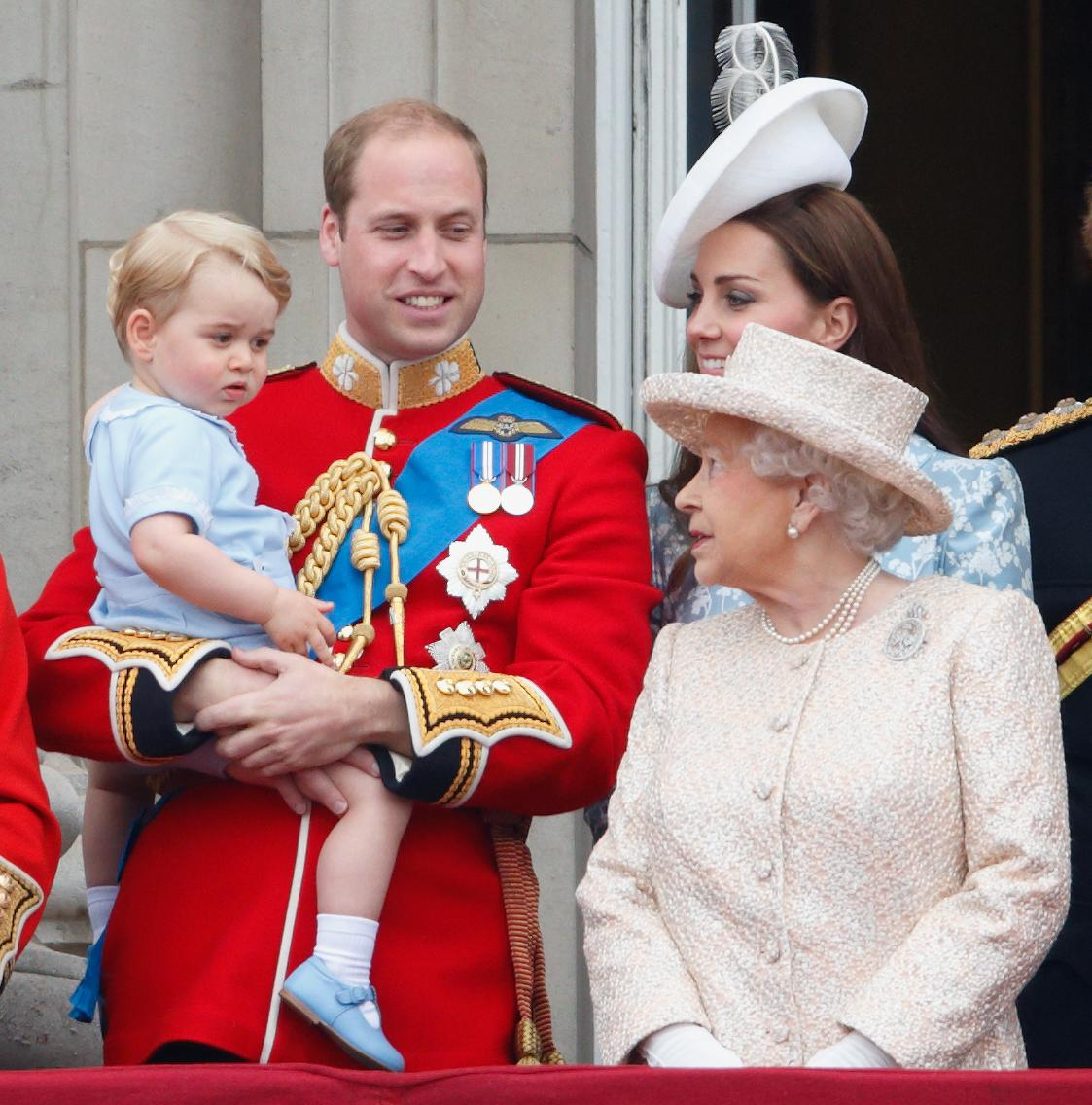 Prince William holds Prince George in his arms as the Queen and Kate Middleton look on on the Buckingham Palace balcony