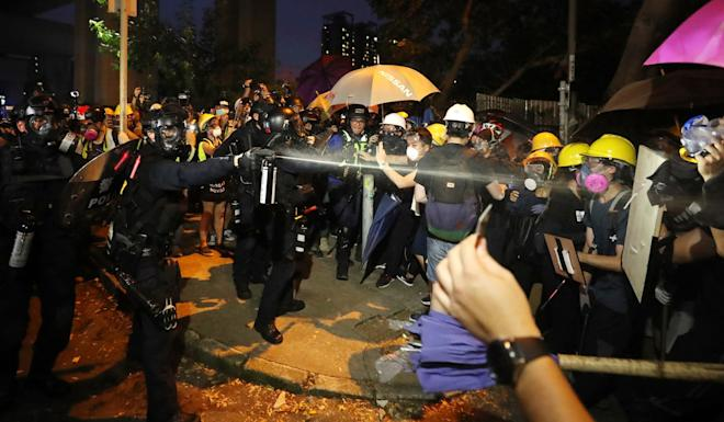 Officers use pepper spray on the angry crowd in Yuen Long. Photo: Sam Tsang