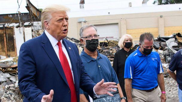 PHOTO: President Donald Trump speaks to the press as he tours an area affected by civil unrest in Kenosha, Wis., Sept. 1, 2020, as John Rode(C), the former owner of Rode's Camera Shop looks on holding a sign. (Mandel Ngan/AFP via Getty Images)