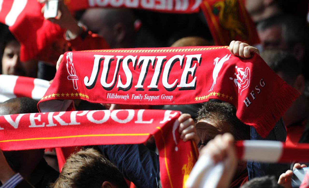 "A scarf with the words ""justice"" is held up by a fan prior to kickoff during the English Premier League soccer match between Liverpool and Manchester City at Anfield in Liverpool, England, Sunday, April 13, 2014. (AP Photo/Clint Hughes)"