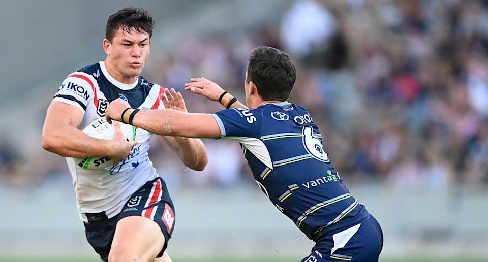 Joseph Manu of the Roosters is tackled by Scott Drinkwater of the Cowboys during the round 18 NRL match between the North Queensland Cowboys and the Sydney Roosters at QCB Stadium in Townsville.