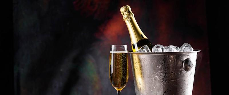 Champagne bottle in bucket with ice and glasses of champagne on dark background. Celebration theme with champagne still life