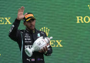 Mercedes driver Lewis Hamilton of Britain holds up his trophy on the podium after placing third after the Hungarian Formula One Grand Prix, at the Hungaroring racetrack in Mogyorod, Hungary, Sunday, Aug. 1, 2021. (AP Photo/Darko Bandic)