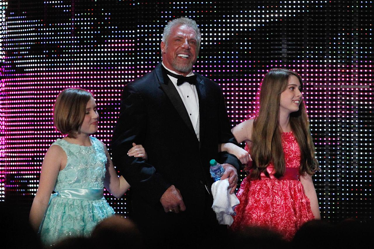 The Ultimate Warrior is escorted by his daughters to the stage during the WWE Hall of Fame Induction at the Smoothie King Center in New Orleans on Saturday, April 5, 2014. (Jonathan Bachman/AP Images for WWE)