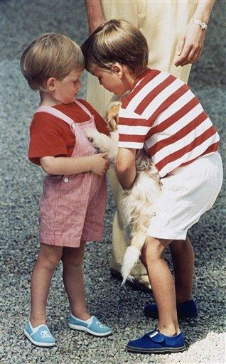 Prince William, right, holds a dog to his younger brother, Prince Harry on August 9, 1987, while on holiday with their parents the Prince and Princess of Wales, unseen. The Royal family is on holiday with King Juan Carlos of Spain, unseen, and his family at his Mediterranean Palace in Majorca. (AP Photo/John Redman)