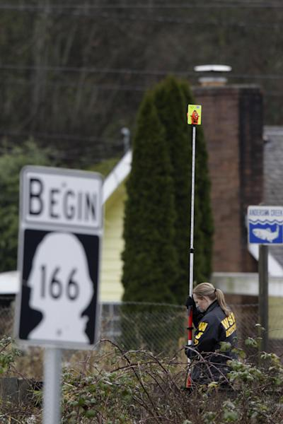 A Washington State Patrol detective investigate the scene where a state trooper making a routine traffic stop was shot and killed early Thursday, Feb. 23, 2012, in Gorst, Wash. (AP Photo/Ted S. Warren)