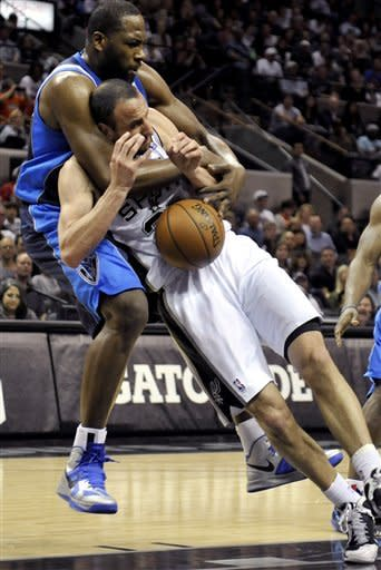 San Antonio Spurs guard Manu Ginobili, of Argentina, is fouled by Dallas Mavericks forward Elton Brand, top, during the first half of an NBA basketball game, Thursday, March 14, 2013, in San Antonio. (AP Photo/Bahram Mark Sobhani)