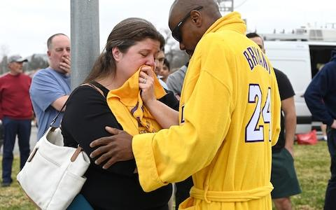 Life long Kobe Bryant fans Amanda and Philip Gordon of the San Fernando Valley, embrace at the at the scene near the hillside where the helicopter carrying Kobe Bryant crashed in Calabasas - Credit: USA Today