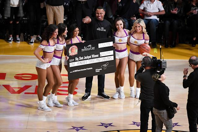 "Fan Suni Strong wins the $100,000 Big Shot Jackpot by making a half court shot during Sunday's game between the <a class=""link rapid-noclick-resp"" href=""/nba/teams/lal/"" data-ylk=""slk:Los Angeles Lakers"">Los Angeles Lakers</a> and the <a class=""link rapid-noclick-resp"" href=""/nba/teams/nyk/"" data-ylk=""slk:New York Knicks"">New York Knicks</a>. (Getty)"