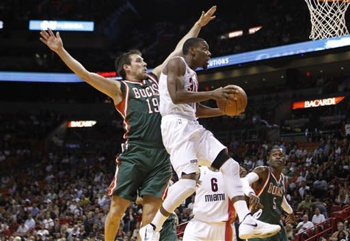 Miami Heat's Norris Cole (30) is fouled by Milwaukee Bucks' Beno Udrih (19) ,of Slovenia, during the first half of an NBA basketball game, Sunday, Jan. 22, 2012, in Miami. At right is Milwaukee Bucks' Stephen Jackson (5). (AP Photo/Lynne Sladky)