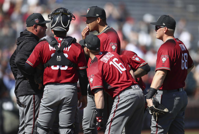 Arizona Diamondbacks' Taijuan Walker, center, speaks with pitching coach Mike Butcher, left, during the first inning of a spring training baseball game against the San Francisco Giants on Tuesday, Feb. 27, 2018, in Scottsdale, Ariz. (AP Photo/Ben Margot)