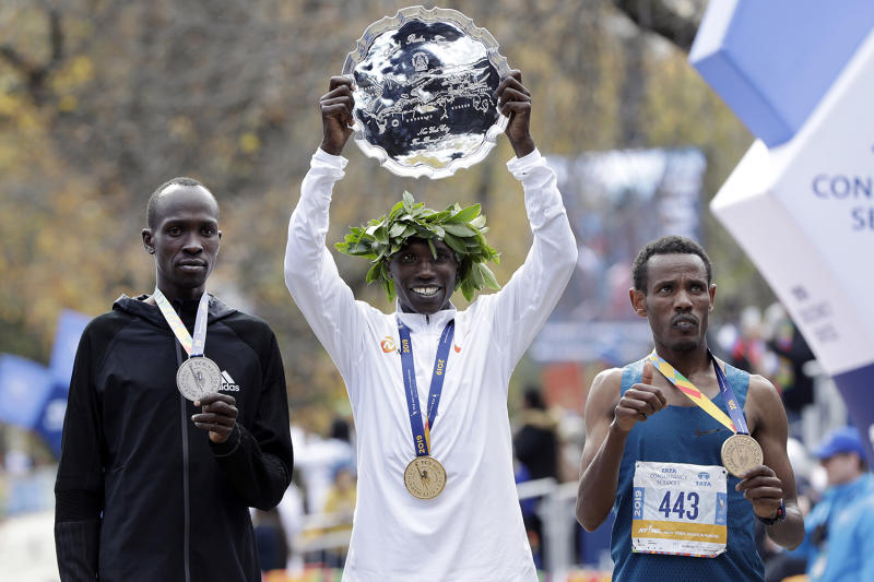 Geoffrey Kamworor, center, of Kenya, men's winner of the New York City Marathon, is flanked by second place finisher and countryman Albert Korir, left, and third place finisher Girma Bekele Gebre, of Ethiopia, as they pose for photos in New York's Central Park, Nov. 3, 2019. (Photo: Richard Drew/AP)