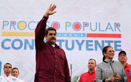 Venezuela's President Nicolas Maduro greets supporters next to his wife Cilia Flores, during a meeting at Miraflores Palace in Caracas
