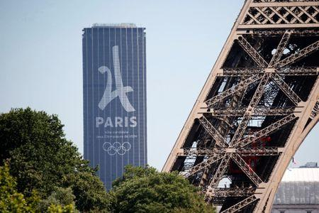 The logo of the Paris candidacy for the 2024 Olympic and Paralympic Games is seen on the Montparnasse tower behind the Eiffel Tower in Paris, France, June 19, 2017.   REUTERS/Charles Platiau