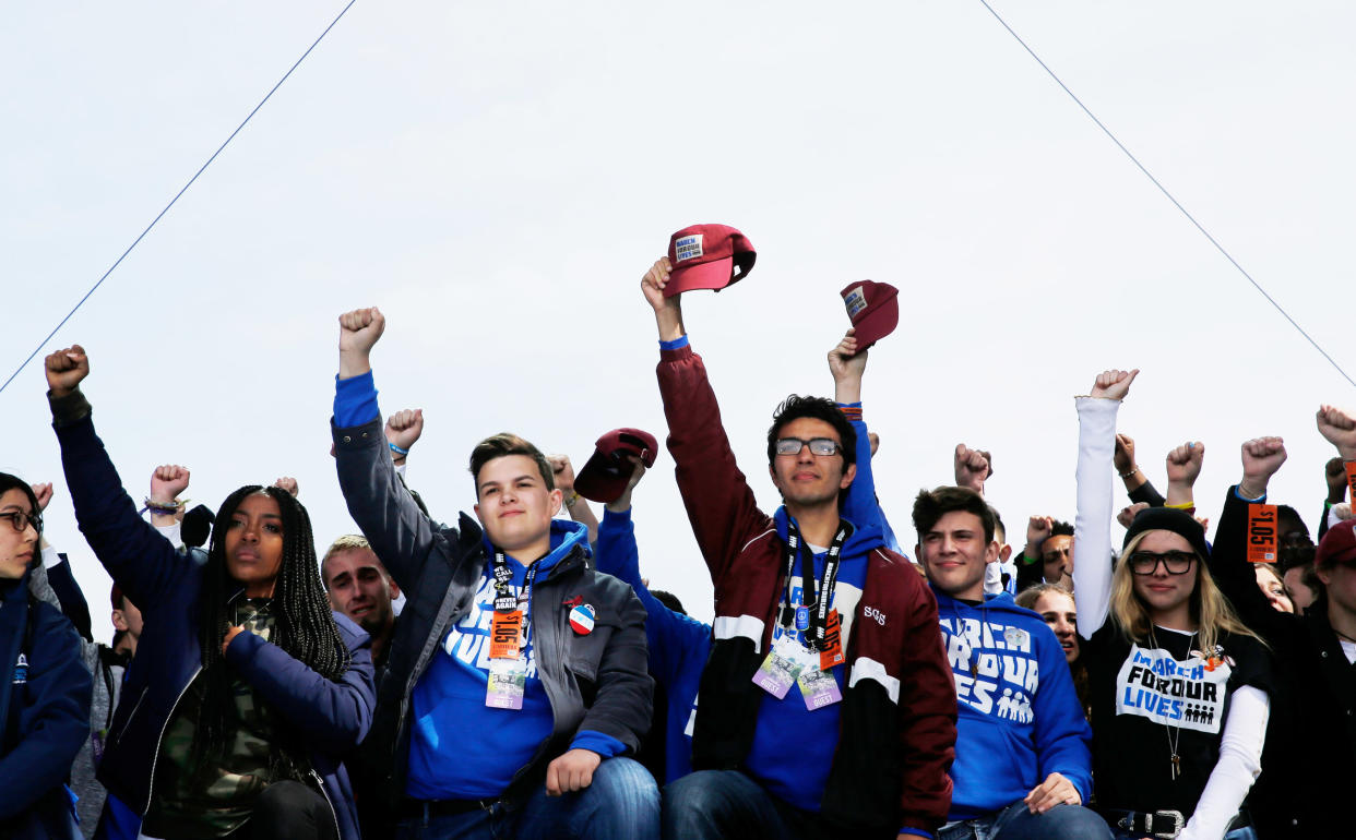 """Students and school shooting survivors hold their fists and hats aloft in solidarity at the conclusion of the """"March for Our Lives"""" event demanding gun control after recent school shootings at a rally in Washington, U.S., March 24, 2018. (Photo: Jonathan Ernst/Reuters)"""