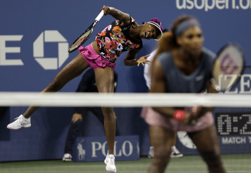 Venus Williams, left, serves as Serena Williams looks on against Lucie Hradecka, of the Czech Republic, and Andrea Hlavackova, of the Czech Republic, during the women's doubles semifinals of the 2013 U.S. Open tennis tournament, Friday, Sept. 6, 2013, in New York. (AP Photo/Charles Krupa)