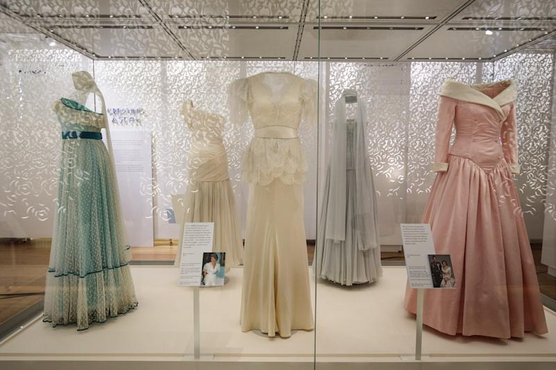 LONDON, ENGLAND - FEBRUARY 22: A 1990 Bruce Oldfield cream satin dress (C) worn by Princess Diana during a visit to the Courtauld Institute of Art in 1990 and a State Banquet at Buckingham Palace in 1991(C) on display next to a 1987 Catherine Walker pink satin evening gown (R) worn by princess Diana for an official portrait in 1987 as well as during official visits to Germany at a press preview at Kensington Palace on February 22, 2017 in London, England. The exhibition 'Diana: Her Fashion Story', which showcases a number of the Princess' dresses and outfits, opens to the public on February 24 as part of events commemorating the life of Princess Diana to mark the 20th anniversary of her death in Paris on August 31st, 1997. (Photo by Jack Taylor/Getty Images)