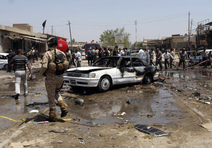 Civilians and security forces gather at the scene of a car bomb attack in the southern Shiite city of Karbala, 50 miles (80 kilometers) south of Baghdad, Iraq, Monday, April. 29, 2013. Five car bombs exploded Monday in predominantly Shiite cities and districts in central and southern Iraq, killing and wounding dozens of people, police said. (AP Photo)