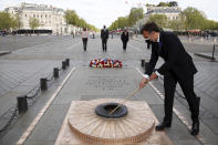 French President Emmanuel Macron lights up the flame at the Tomb of the Unknown soldier during a ceremony at the Arc de Triomphe to mark the 76th anniversary of the end of World War II, in Paris, Saturday, May 8, 2021.(Christian Hartmann/Pool via AP)