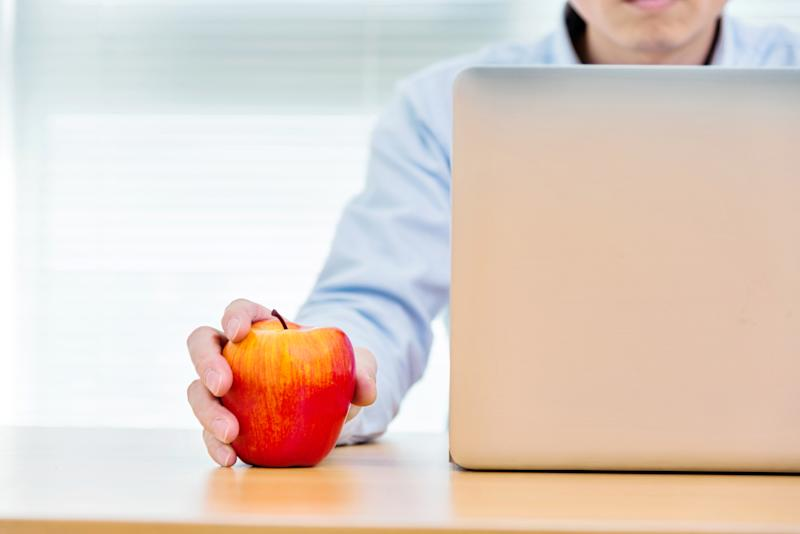 Businessman holding an apple and working on laptop.