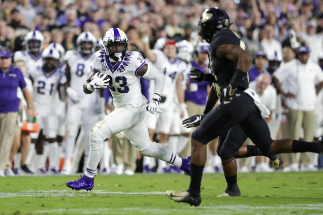 TCU running back Sewo Olonilua (33) looks to get past Purdue safety Jalen Graham (6) during the first half of an NCAA college football game in West Lafayette, Ind., Saturday, Sept. 14, 2019. (AP Photo/Michael Conroy)
