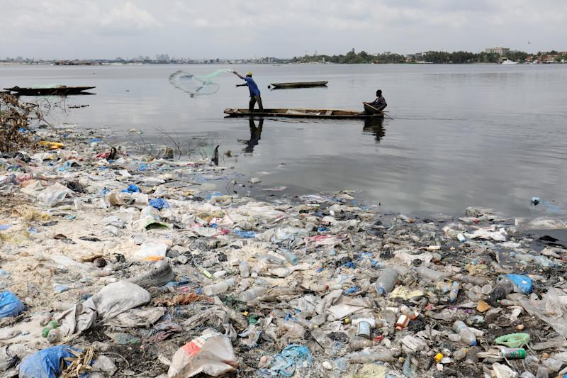 Men fish as plastic items and other debris are seen on the shore in Abidjan, Ivory Coast. (Photo: Thierry Gouegnon/Reuters)