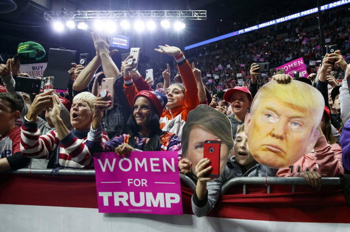 James Crockett, 10, holds a mask of President Donald Trump and cheers as the president arrives for a rally at Allen County War Memorial Coliseum, Monday, Nov. 5, 2018, in Fort Wayne, Ind.. (AP Photo/Carolyn Kaster)