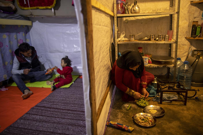 Syrian refugee Ayesha al-Abed, 21, right, prepares food as her Husband Raed Mattar, 24, left, plays with their daughter Rayan, 18 months old, before they break their fast on the first day of fasting month of Ramadan, at an informal refugee camp, in the town of Bhannine in the northern city of Tripoli, Lebanon, Tuesday, April 13, 2021. (AP Photo/Hassan Ammar)