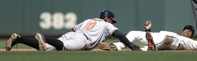 Baltimore Orioles' Adam Jones, left, gets back to second base before the tag of San Francisco Giants' Joaquin Arias, right, in the sixth inning of a baseball game, Saturday, Aug. 10, 2013, in San Francisco. (AP Photo/Ben Margot)