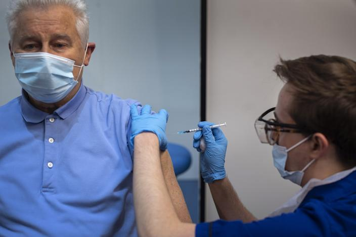 A man receives the first of two Pfizer/BioNTech Covid-19 vaccine jabs, at Guy's Hospital in London, on the first day of the largest immunisation programme in the UK's history. Care home workers, NHS staff and people aged 80 and over began receiving the jab this morning.