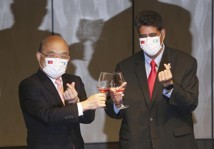 Palau President Surangel Whipps, right, cheers with Taiwan Premier Su Tseng-chang at a dinner party in Taipei, Taiwan, Monday, March 29, 2021. Whipps arrived in Taiwan on Sunday, for a five-day visit to kick-off the Taiwan-Palau travel bubble that starts April 1. (AP Photo/Chiang Ying-ying)