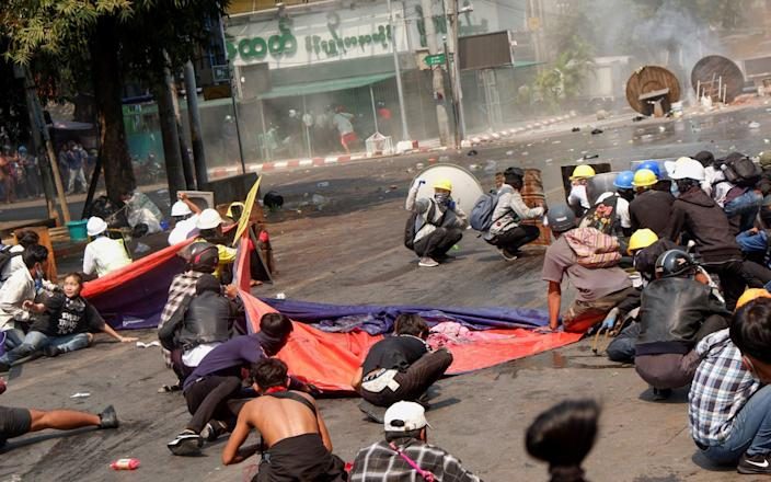 Protesters lie on the ground after police open fire to disperse an anti-coup protest - REUTERS