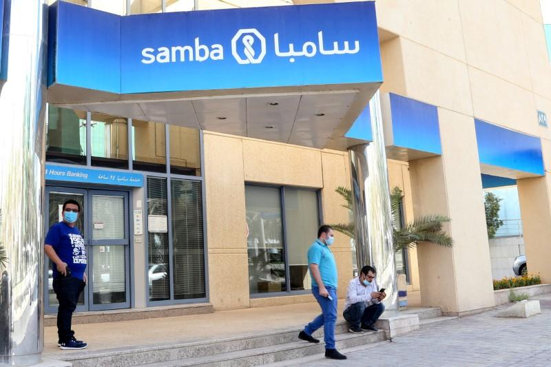 People wearing protective face masks are seen outside Samba bank as the government eases lockdown restrictions amid the coronavirus disease (COVID-19) outbreak, in Riyadh