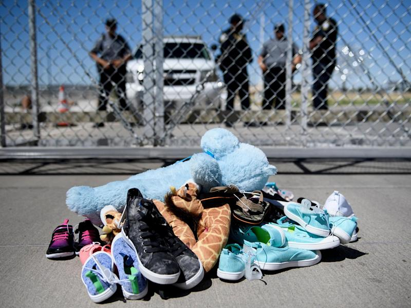 Security personnel stand before shoes and toys left at the Tornillo Port of Entry where children crossing the border without proper papers have been housed after being separated from adults: Brendan Smialowski/AFP via Getty Images