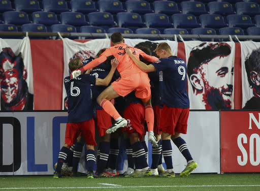 New England Revolution players celebrate a goal by forward Gustavo Bou, obscured, during the second half of an MLS soccer match against the Montreal Impact, Friday, Nov. 20, 2020, in Foxborough, Mass. The Revolution won 2-1. (AP Photo/Stew Milne)