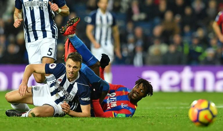West Bromwich Albion's Jonny Evans (L) clashes with Crystal Palace's Wilfried Zaha during their English Premier League match, at The Hawthorns stadium in West Bromwich, on December 2, 2017