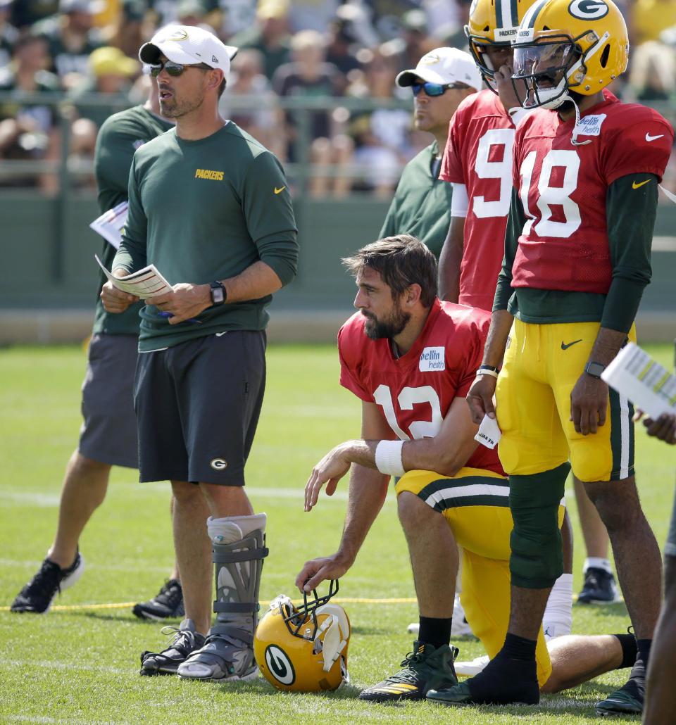 Green Bay Packers head coach Matt LaFleur, left, watches a drill with quarterbacks Aaron Rodgers (12), DeShone Kizer (9) and Manny Wilkins (18) during a joint NFL football practice with the Houston Texans, Monday, Aug 5, 2019, in Green Bay, Wis. (AP Photo/Mike Roemer)