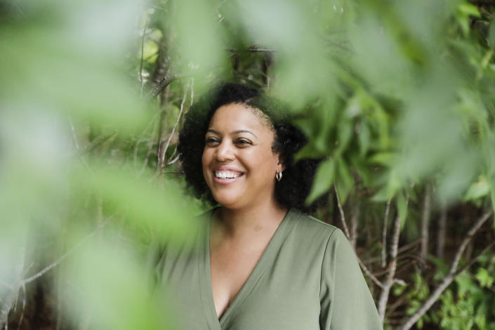 """FILE - In this Friday, July 24, 2020 file photo, Charisse Davis, who serves on the Cobb County School Board, poses for a portrait in Marietta, Ga. On the Saturday that news organizations called the presidential race for Joe Biden, Davis popped a bottle of champagne, despite a nagging sense of sadness, then packed the family into the car to head into downtown Atlanta and join thousands dancing in the street. She decided to just enjoy victory. """"We'll go back to worrying about humanity tomorrow,"""" she said to her family as they climbed in the car. And then tomorrow arrived, and the worry roared back. (AP Photo/Brynn Anderson)"""