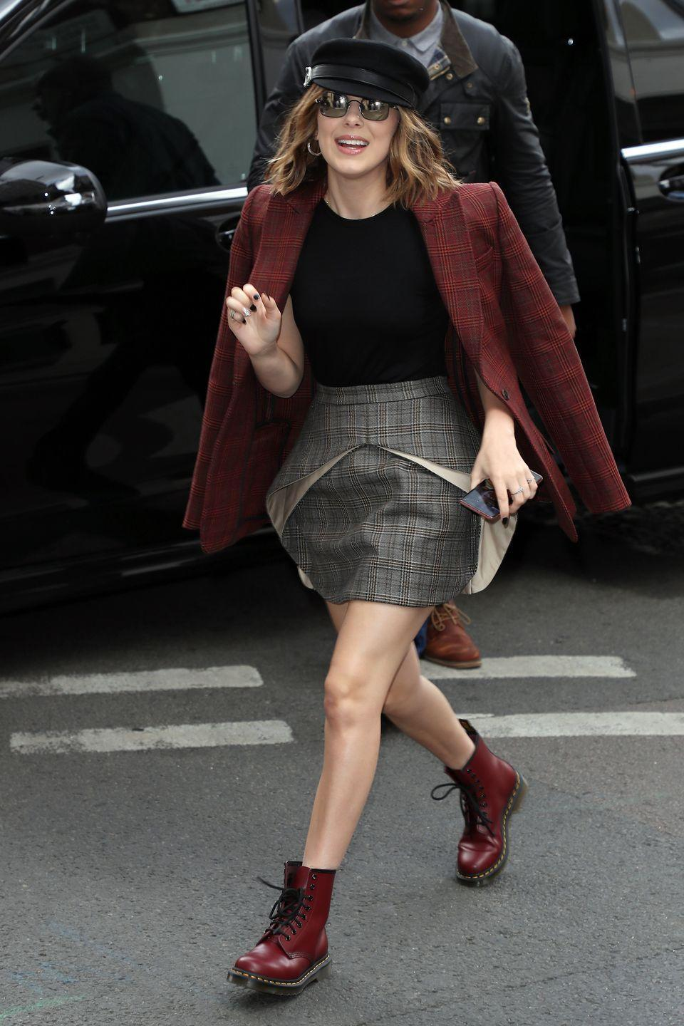 <p>Perhaps previewing her fall fashion to come, Millie Bobby Brown headed to KISS FM UK radio studios in a plaid jacket and skirt, completed with burgundy combat boots and a black cap. </p>