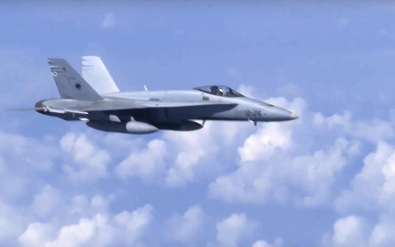 In this video grab taken from a footage on Aug. 13, 2019, and distributed by Russian Defense Ministry Press Service, a NATO F-18 warplane is viewed from the window of a passenger plane carrying Russian Defense Minister Sergei Shoigu over the Baltic See.  A video aired on Russian state television shows a fighter jet warding off a NATO military aircraft that approached a passenger plane carrying Russia's defense minister. (Russian Defense Ministry Press Service via AP)