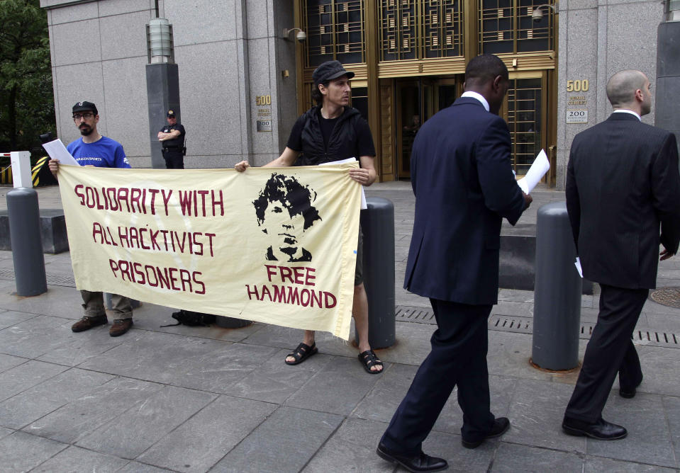 FILE - In this Monday, May 14, 2012, file photo, protesters stand in front of the federal courthouse during the arraignment of hacker Jeremy Hammond, in New York. Hammond, who is serving a 10-year prison sentence for breaking into computer systems of security firms and law-enforcement agencies, will serve out the remainder of his term in a Chicago halfway house, a U.S. Bureau of Prison spokesman said Wednesday, Nov. 18, 2020. (AP Photo/Seth Wenig, File)